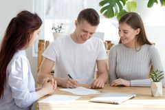 Family signed a contract, new home concept. Three young millennial people sitting at the desk in office agency. Married family couple happy smiling sign a stock photo