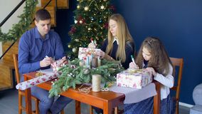 Family signing christmas gift boxes on xmas eve stock video footage
