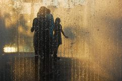 Family in silhouette enjoy pavement fountain royalty free stock images