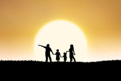 Family silhouette on sunset. Silhouette of family walking on the field under the sunset Royalty Free Stock Photography