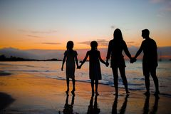 Family silhouette in the sunset at the beach. Family silhouette in the sunset on beach vacation Stock Images