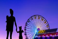 Family silhouette in a theme park looking at the ferris wheel mother with her little daughter and baby stock photo