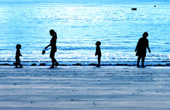 Family silhouetted on a blue evening beach royalty free stock image