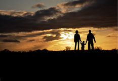 Family silhouetted at sunset royalty free stock photography