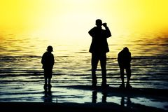 Family silhouettes. Silhouettes of father and two sons looking at the ocean Royalty Free Stock Photography