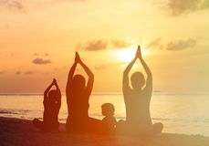 Family silhouettes doing yoga at sunset Stock Photo