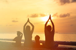 Family silhouettes doing yoga at sunset sea Stock Photos