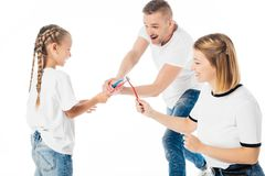Family in similar clothing playing with toothbrushes. Isolated on white stock photo