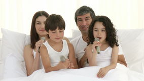 Family singing in bed with microphones Stock Photo