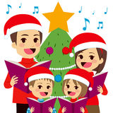 Family Singing Christmas Carols. Happy family singing carols in front of Christmas tree at home Stock Image