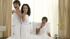 Family singing and dancing karaoke on bed with microphones stock video