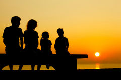 Family sit on bench on beach. Father with mother and two children  sit on  bench on  beach in  evening and converse Royalty Free Stock Photo