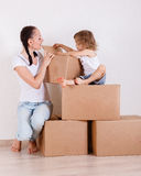 Family sit in a room on the boxes. Stock Photo