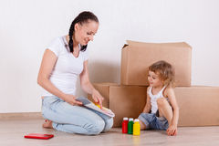Family sit in a room near the boxes. Stock Photo