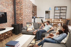 Family Sit On Sofa In Open Plan Lounge Watching Television Royalty Free Stock Images