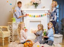 Family siting near a fireplace on cozy carpet and playing with cute bunny. Stock Photo
