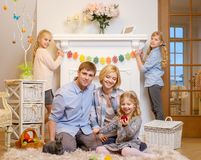 Family siting near a fireplace on cozy carpet and playing with cute bunny. Royalty Free Stock Photos