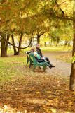 Family sits in autumn park on bench Royalty Free Stock Image