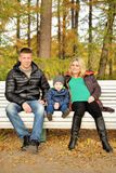 Family sits in autumn park on bench Royalty Free Stock Images