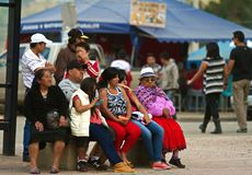Several Generations of Family at a Festival in Ecuador. Family sits on a bench together. Grandmother dressed in traditional clothing as mother dressed in more Stock Photography