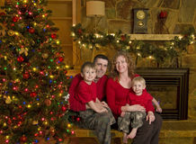 Family Sits beside Christmas Tree Stock Images