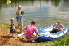 Family sits down in an inflatable boat Royalty Free Stock Images