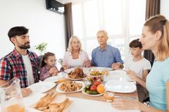 The family is sitting at the table for Thanksgiving and praying with closed eyes holding hands. The family sits at a festive table and pray with closed eyes Royalty Free Stock Images