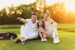 The family sits on the grass on the golf course, the man points to the side, and the wife and daughter look there Stock Photography