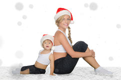 Family sits in snow in Santa hats Royalty Free Stock Photo