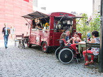 Family sits at table near red food truck on the South Bank, Lond Royalty Free Stock Photo