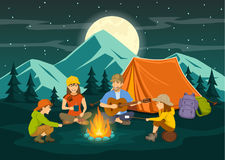Family sitting around campfire and tent, night scene. Family sitting around campfire and tent, cooking sausages and marshmallow, singing, having fun, camping Stock Photo