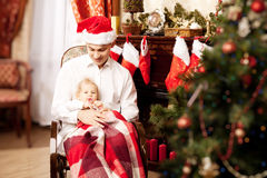 Family sitting around the Christmas tree. Dad and baby in the Ne Royalty Free Stock Photography