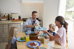 Family sitting around kitchen table serving lunch Stock Photo