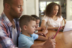 Family Sitting Around Table At Home Using Technology Royalty Free Stock Image