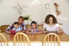 Family Sitting Around Table At Home Using Technology Royalty Free Stock Photography