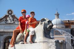 Family are sitting astride fountain. Young mother, young daughter and son are sitting astride fountain in form of lion on Piazza del Popolo in Rome, Italy Royalty Free Stock Image