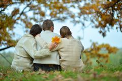 Family sitting in autumn park Stock Photography