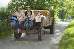 Family Sitting On Back Of Trailer On Country Lane Royalty Free Stock Photos