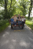 Family Sitting On Back Of Trailer On Country Lane Royalty Free Stock Image