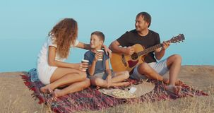 Family sitting by the on the beach in the evening and playing guitar. stock video footage