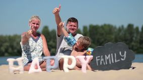 Family sitting on the beach and giving thumbs up Royalty Free Stock Images