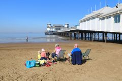 Family sitting on beach by pier. A family sitting on the sand beach by the Grand Pier at Weston Super Mare in North Somerset, England Royalty Free Stock Image