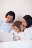 Family sitting on the bed with laptop Royalty Free Stock Image