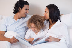Family sitting on the bed reading a book Royalty Free Stock Image