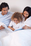 Family sitting on the bed reading a story Royalty Free Stock Photography