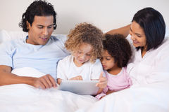Family sitting on the bed using tablet Stock Image