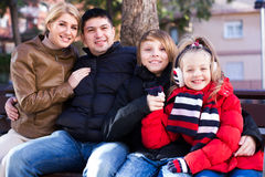 Family sitting on bench outdoors Royalty Free Stock Image