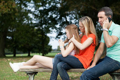 Family sitting on a bench Royalty Free Stock Image