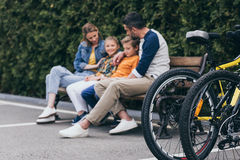 Family sitting on bench at park, selective focus on bicycles on foreground. Casual family sitting on bench at park, selective focus on bicycles on foreground Royalty Free Stock Photography