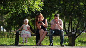 Family sitting on a bench with smartphones stock video footage